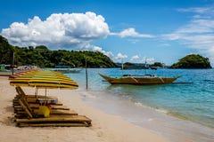 Los salones de Sun con los paraguas en Ilig Iligan varan, isla de Boracay, Filipinas foto de archivo