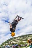 Los saltos adolescentes con la vespa sobre una rampa y realizan un salto Imagen de archivo
