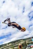 Los saltos adolescentes con la vespa sobre una rampa y realizan un salto Imagenes de archivo