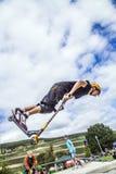 Los saltos adolescentes con la vespa sobre una rampa y realizan un salto Imágenes de archivo libres de regalías