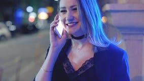 Los saludos de la muchacha del feliz cumpleaños llaman por teléfono a noche de la calle almacen de metraje de vídeo