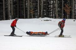 Los salvadores del esquí están transportando al esquiador dañado Fotos de archivo libres de regalías