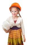 Los seis años de muchacha de la sonrisa en el casco de protección se colocan con el rollo de dibujos Foto de archivo