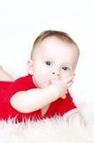 Los seis-meses pensativos de bebé sostienen los fingeres en boca Imagen de archivo