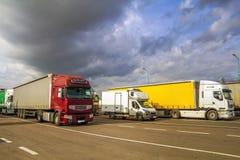 Los semi-camiones y los remolques grandes modernos coloridos de diferente hacen Imagenes de archivo