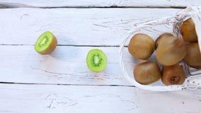 Los seres humanos dan tajar la fruta de kiwi en el fondo rústico blanco cerca de la cesta de frutas dispersada metrajes