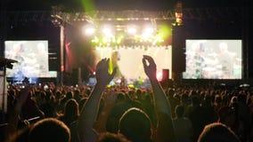 Los seres humanos que saltan en el festival de la roca, luces coloridas en la etapa, iluminación colorida durante concierto de ro almacen de video