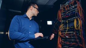 Los servidores del ordenador están consiguiendo examinados por un ingeniero con un ordenador portátil almacen de video