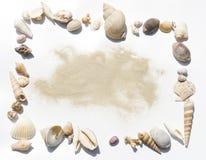 Los shelles enmarcan con la arena Foto de archivo libre de regalías