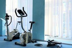 Los simuladores de los deportes se colocan cerca de la ventana con las persianas Bicicletas estáticas para la actividad física Re foto de archivo libre de regalías