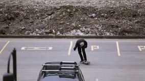 Los skateres que montan en espacio de estacionamiento, hacen tirón patín Manía extrema metrajes