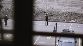Los skateres que montan en espacio de estacionamiento, hacen trucos patín Manía extrema almacen de video