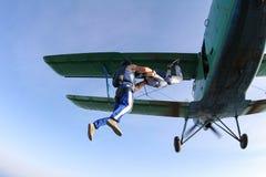 Los Skydivers han saltado de un biplano verde imágenes de archivo libres de regalías