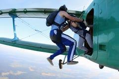 Los Skydivers son el saltar de un biplano verde foto de archivo