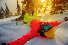Los snowboarders de las chicas jóvenes gozan en invierno Foto de archivo libre de regalías