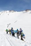Los snowboarders del grupo suben la montaña para el freeride Fotos de archivo