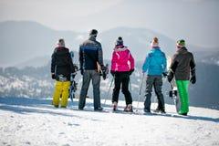 Los Snowboarders disfrutan del paisaje blanco como la nieve de montañas y de delanteras fotografía de archivo
