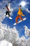 Los Snowboarders que saltan contra el cielo azul Imagen de archivo libre de regalías