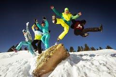 Los Snowboarders saltan en el contexto del cielo azul en montañas foto de archivo