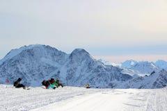 Los Snowboarders se sientan en nieve en las cuestas de la montaña Elbrus el Cáucaso imagen de archivo libre de regalías