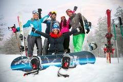 Los snowboarders y los esquiadores felices de los amigos se divierten en la cuesta Fotos de archivo libres de regalías