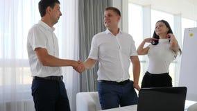 Los socios comerciales felices aplauden sus manos que se sientan antes de ordenador portátil en espacio de oficina almacen de video