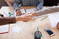 Los socios comerciales sacuden las manos en la sala de conferencias imagen de archivo libre de regalías