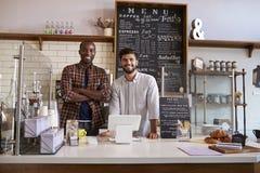 Los socios comerciales se colocan detrás del contador en una cafetería fotografía de archivo