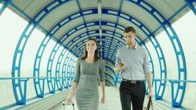 Los socios comerciales van con equipaje en el terminal de la estación o del aeropuerto Viaje de negocios, trabajo del equipo almacen de video