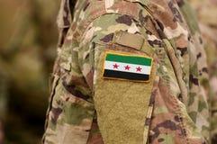 Los soldados arman con la bandera usada por la oposición siria y siria imagenes de archivo