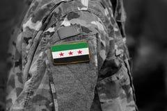 Los soldados arman con la bandera usada por la oposición siria y siria fotografía de archivo