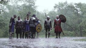 Los soldados de la edad medieval con la armadura y las armas se están colocando bajo la lluvia almacen de metraje de vídeo