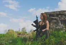 Los soldados de la muchacha que miran en la distancia que se coloca al lado del arma Imagenes de archivo