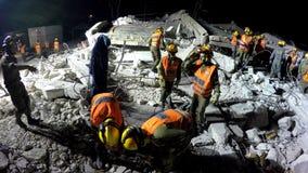 Los soldados de la seguridad de patria evacuan a gente herida tsunami del ataque del cohete del terremoto Foto de archivo