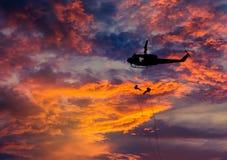 Los soldados de la silueta en la acción rappelling suben abajo del helicóptero con terrorismo del contador de la misión militar Foto de archivo libre de regalías