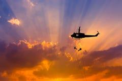 Los soldados de la silueta en la acción rappelling suben abajo del helicóptero con terrorismo del contador de la misión militar Imagen de archivo