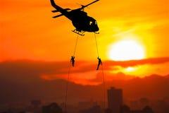 Los soldados de la silueta rappel abajo para atacar del helicóptero encendido con puesta del sol y el espacio de la copia añade h imagen de archivo