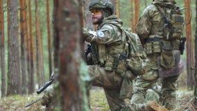 Los soldados en camuflaje con las armas del combate hacen su manera fuera del bosque, con el objetivo de capturarlo, los militare almacen de video