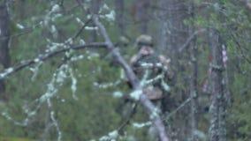 Los soldados en camuflaje con las armas del combate hacen su manera fuera del bosque, con el objetivo de capturarlo, los militare almacen de metraje de vídeo