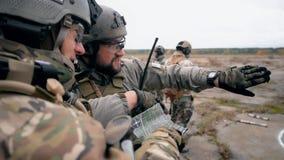 Los soldados en uniforme están viendo un mapa metrajes