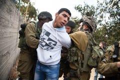 Los soldados israelíes arrestan al palestino Imagen de archivo