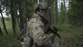 Los soldados pasan a través del bosque Militares con las armas enviadas a los matorrales del verde juego del airsoft metrajes