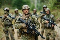 Los soldados que se colocan con el equipo y están mirando adelante Fotografía de archivo libre de regalías