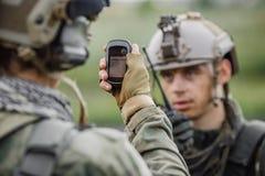Los soldados que sostienen el navegador disponible y determinan la ubicación o fotos de archivo libres de regalías
