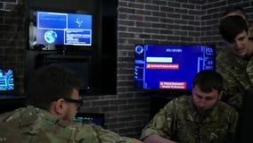 Los soldados serios en uniforme, en campo establecen jefatura, guerra cibernética almacen de video