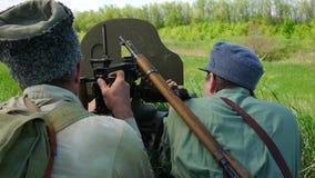 Los soldados tiran de una ametralladora HD almacen de video