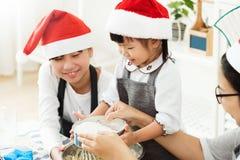 Los sombreros asiáticos felices de Papá Noel del desgaste de la familia que preparan la pasta, cuecen arrullan Imagen de archivo