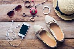 Los sombreros, los zapatos y los accesorios a vestirse mintieron en el piso de madera para el viaje - tono del vintage Fotografía de archivo