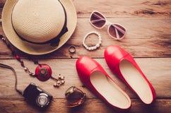Los sombreros, los zapatos y los accesorios a vestirse mintieron en el piso de madera para el viaje - tono del vintage Imágenes de archivo libres de regalías