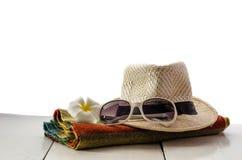 Los sombreros, vidrios, bufandas, flores se colocan en un piso de madera con el fondo blanco Imagen de archivo